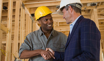 two men in hard hats on construction site shaking hands